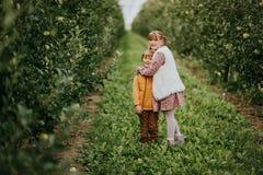 Deux enfants drôles jouant dans le champ de pommiers vert Photographie stock
