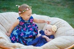 Deux enfants drôles s'asseyant dans la lumière molle président ensemble au printemps le parc images libres de droits