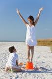 Deux enfants effectuant des pâtés de sable sur la plage Photographie stock libre de droits