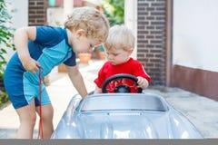 Deux enfants en bas âge de petits frères jouant avec des véhicules Images libres de droits