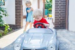 Deux enfants en bas âge de petits frères jouant avec des véhicules Photographie stock libre de droits