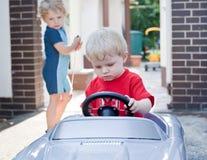 Deux enfants en bas âge de petits frères jouant avec le grand véhicule de jouet Image stock