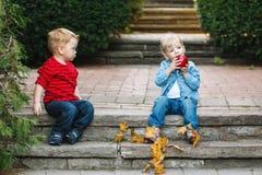 Deux enfants en bas âge drôles adorables mignons caucasiens blancs d'enfants reposant partager ensemble mangeant de la nourriture Photos libres de droits