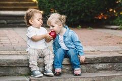 Deux enfants en bas âge drôles adorables mignons caucasiens blancs d'enfants reposant partager ensemble mangeant de la nourriture Photographie stock