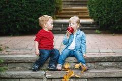 Deux enfants en bas âge drôles adorables mignons caucasiens blancs d'enfants reposant partager ensemble mangeant de la nourriture Images stock