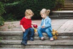 Deux enfants en bas âge drôles adorables mignons caucasiens blancs d'enfants reposant partager ensemble mangeant de la nourriture Image libre de droits