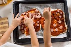 Deux enfants en bas âge faisant la pizza faite maison Image stock