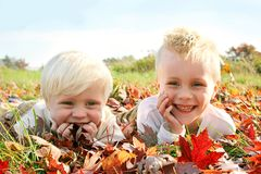Deux enfants en bas âge heureux jouant dehors dans des feuilles d'automne Images libres de droits