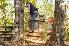 Deux enfants en bas âge jouant sur une vieille porte en bois Photo stock