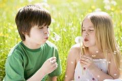 Deux enfants en bas âge s'asseyant à l'extérieur Photographie stock libre de droits
