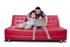 Deux enfants et Internet de lecture rapide de papa en ligne Photo stock