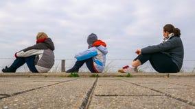 Deux enfants et une femme qui s'asseyent sur les pavillons et observent la Mer du Nord, des Pays-Bas, habillés profondément ave photos stock