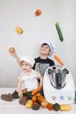 Deux enfants faisant cuire avec une machine futuriste Images libres de droits