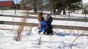 Deux enfants font grand Snowball appréciant Sunny Weather Outdoors chaud La soeur et le frère jouent en hiver clips vidéos
