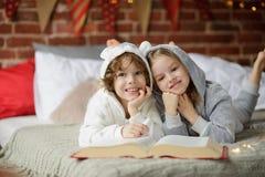 Deux enfants, frère et soeur, ont lu des contes de Noël Photo stock
