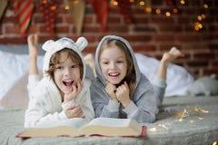 Deux enfants, frère et soeur, ont lu des contes de Noël Image stock