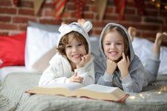 Deux enfants, frère et soeur, ont lu des contes de Noël Photographie stock libre de droits