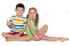 Deux enfants gais sur le blanc Image stock