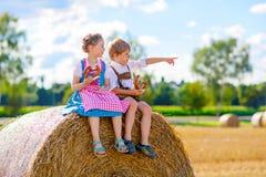 Deux enfants, garçon et fille dans des costumes bavarois traditionnels dans le domaine de blé Images libres de droits