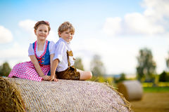 Deux enfants, garçon et fille dans des costumes bavarois traditionnels dans le domaine de blé Photos libres de droits