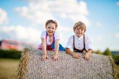 Deux enfants, garçon et fille dans des costumes bavarois traditionnels dans le domaine de blé Photos stock