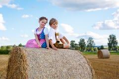 Deux enfants, garçon et fille dans des costumes bavarois traditionnels dans le domaine de blé Photographie stock libre de droits