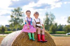 Deux enfants, garçon et fille dans des costumes bavarois traditionnels dans le domaine de blé Images stock