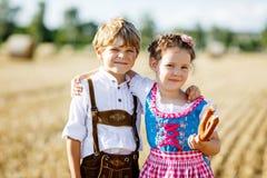 Deux enfants, garçon et fille dans des costumes bavarois traditionnels dans le domaine de blé Image libre de droits