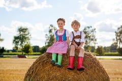 Deux enfants, garçon et fille dans des costumes bavarois traditionnels dans le domaine de blé Image stock