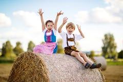 Deux enfants, garçon et fille dans des costumes bavarois traditionnels dans le domaine de blé avec des balles de foin Images stock