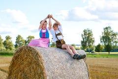 Deux enfants, garçon et fille dans des costumes bavarois traditionnels dans le domaine de blé avec des balles de foin Image stock