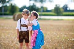 Deux enfants, garçon et fille dans des costumes bavarois traditionnels dans le domaine de blé avec des balles de foin Photographie stock