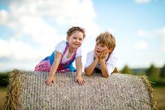 Deux enfants, garçon et fille dans des costumes bavarois traditionnels dans le domaine de blé avec des balles de foin Photo stock