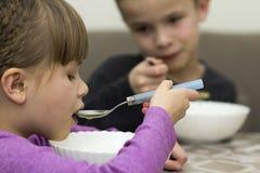 Deux enfants garçon et fille mangeant de la soupe Photographie stock libre de droits