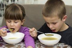 Deux enfants garçon et fille mangeant de la soupe Photo libre de droits