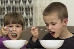 Deux enfants garçon et fille mangeant de la soupe avec la cuillère des WI d'un plat Image stock