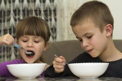 Deux enfants garçon et fille mangeant de la soupe avec la cuillère des WI d'un plat Photographie stock libre de droits