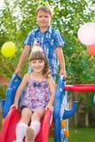 Deux enfants glissant au terrain de jeu photographie stock