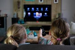 Deux enfants glissant par les applis à une TV futée de retour des enfants avec le foyer sur les enfants photo libre de droits