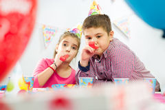 Deux enfants heureux ayant l'amusement à la fête d'anniversaire Photographie stock libre de droits