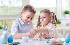 Deux enfants heureux ayant l'amusement pendant la peinture eggs pour Pâques dedans Photographie stock