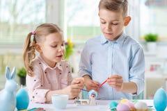 Deux enfants heureux ayant l'amusement pendant la peinture eggs pour Pâques dedans Photos stock