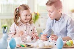 Deux enfants heureux ayant l'amusement pendant la peinture eggs pour Pâques dedans Images stock