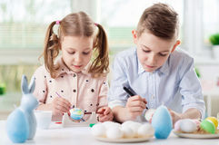 Deux enfants heureux ayant l'amusement pendant la peinture eggs pour Pâques dedans Photo stock