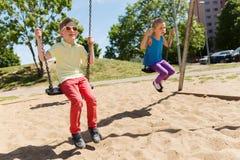 Deux enfants heureux balançant sur l'oscillation au terrain de jeu Photos stock