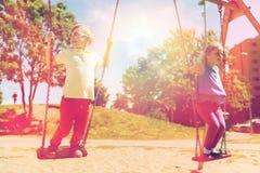 Deux enfants heureux balançant sur l'oscillation au terrain de jeu Photographie stock libre de droits