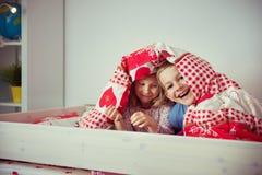 Deux enfants heureux d'enfant de mêmes parents ayant l'amusement dans le lit superposé Photo stock