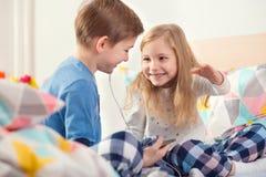 Deux enfants heureux d'enfants de mêmes parents ayant l'amusement et la musique de écoute avec photo stock