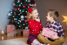 Deux enfants heureux dans la soirée du Nouveau an avec des présents s'approchent de la nouvelle année T Photo libre de droits