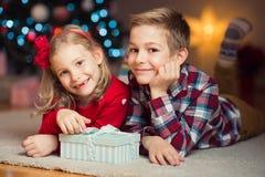 Deux enfants heureux dans la soirée du Nouveau an avec des présents s'approchent de la nouvelle année T Photo stock